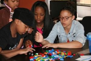 Tre personer bygger med Lego tillsammans.