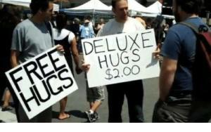 Två personer med varsin skylt: Gratis kramar respektive Lyxkramar 2 dollar.